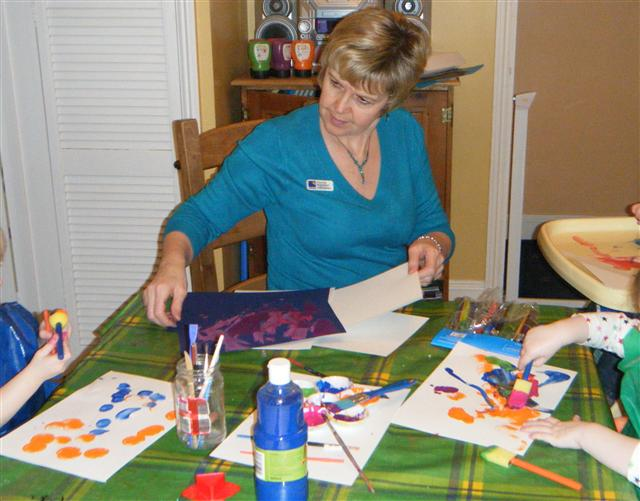 Denise with kids painting at table